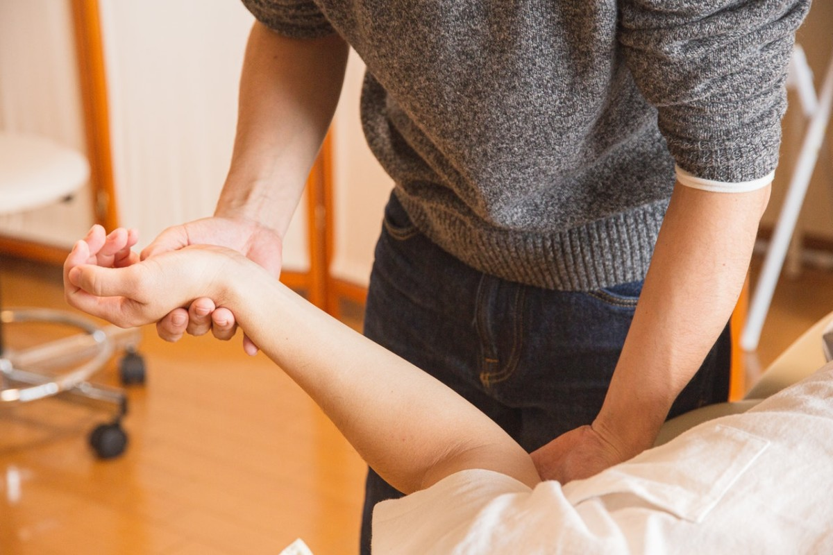 woman massaging hand and wrist of patient